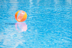 An orange ball in the blue water swimming pool Royalty Free Stock Photography