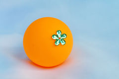 Orange ball decorate by plastic flower. The orange ball decorate by plastic flower.Invent it be a toy for children Stock Photography