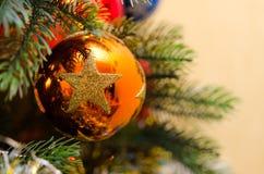 Orange Ball mit goldenem Stern auf künstlichem Weihnachtsbaum Stockbild