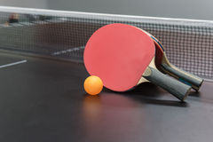 Orange ball with red table tennis racket on black table Royalty Free Stock Photo