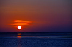 Orange Ball of the Sun Dipping towards Horizon at Sunset Stock Images