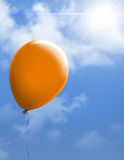 Orange balloon in bright sky Stock Photography
