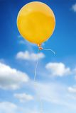 Orange balloon with rope flying in the sky Stock Photography