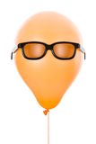 Orange balloon with sunglasses. Isolated on white Royalty Free Stock Image