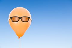Orange Balloon with sunglasses against blue sky with copyspace Stock Photography