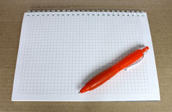 Orange ballpoint pen on the Notepad. With a blank page in the box. Notepad on rough brown paper Royalty Free Stock Photo