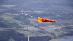 Orange banner flag tied to a pole while swaying mid-air measuring wind speed stock video footage