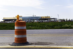 Orange Barrell. Orange and white barrell in a roadway in front of parking lot full of cars stock photography