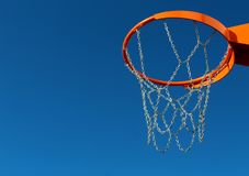 Orange basketball rim and chain metal net against blue sky. Orange basketball rim hoop and chain metal net against blue sky Stock Image