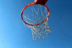 Orange basketball rim hoop and white net against blue sky Stock Photography