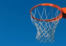 Orange basketball rim and white net against blue sky Royalty Free Stock Photo