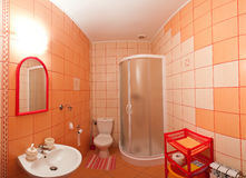 Orange bathroom. Wide angle view of an orange tiled bathroom Royalty Free Stock Photography