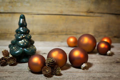 Orange baubles, fir cones and christmas tree on wood Stock Photos