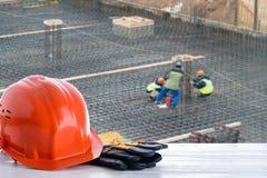 Orange Bausturzhelm auf dem Hintergrund des Hochbaus Lizenzfreie Stockfotos