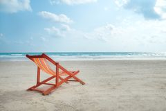 An orange beach chair. An orange beach chair rests on the white sand of the beach and Bright blue sea with white clouds, at Rayong Thailand royalty free stock image