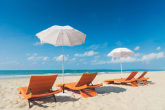 Orange beach chairs and parasols on sandy beach with cloudy blue Stock Image