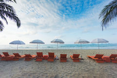 Orange beach chairs and parasols on sandy beach with cloudy blue Royalty Free Stock Images