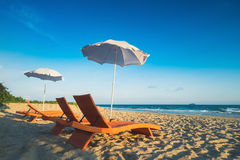 Orange beach chairs and parasols on sandy beach with cloudy blue Royalty Free Stock Photography