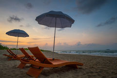 Orange beach chairs and parasols on sandy beach with morning sky Royalty Free Stock Photography