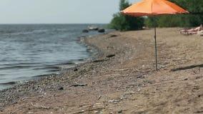Orange beach umbrella. On seaside stock video