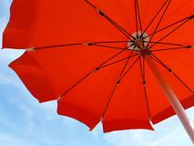Orange beach umbrella in the wind. Under blue sky Royalty Free Stock Photography