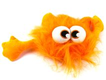 An orange beast with big eyes. Orange toy monster with long hair and bulging eyes Royalty Free Stock Image