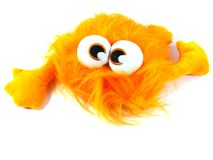 An orange beast with big eyes. Orange toy monster with long hair and bulging eyes Royalty Free Stock Photography