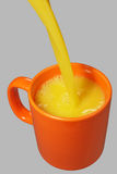 Orange Becher- und Saftstrom Stockbilder