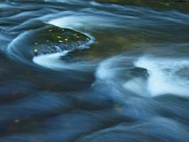 Orange beech leaves on mossy stone below increased water level. Blurred motion of waves around the stone. Royalty Free Stock Image
