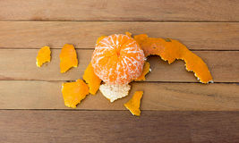 1Orange being peeled on the wooden floor. Royalty Free Stock Photo
