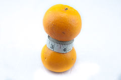 Orange being squeezed by measure tape. It could be useful to promote weight loss and fitness campaign Stock Photo