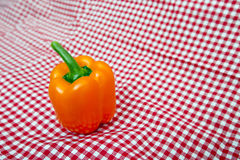 Orange Bell Pepper against red and white chequered cloth Stock Photography