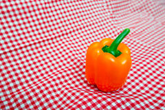Orange Bell Pepper against red and white chequered cloth Royalty Free Stock Photography