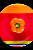 Orange Bell Pepper Sitting on a Colorful Dish Royalty Free Stock Photos