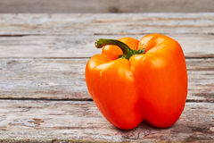 Orange bell pepper on wood. Royalty Free Stock Images