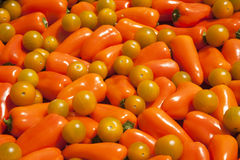 Orange bell peppers and yellow tomatoes background Royalty Free Stock Photo