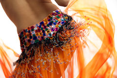 Orange belly dancer. Belly of the woman dancing in the orange dancing dress Royalty Free Stock Photography