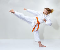 With an orange belt, an athlete trains a kick Royalty Free Stock Photos