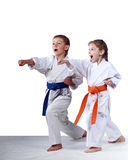 With orange belt girl and boy with a blue belt are hitting blows arms Royalty Free Stock Photography