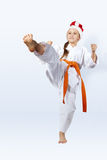 With orange belt girl in the cap of Santa Claus strikes a blow Royalty Free Stock Photography