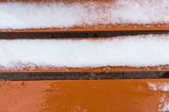 Orange bench covered in snow Stock Image