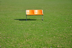 Orange bench on lawn Royalty Free Stock Photo