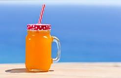 Orange beverage in a handled mason jar Royalty Free Stock Photos