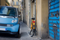 Orange bicycle and blue car on the street in Italy Stock Photo