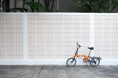 Orange bicycle parks in front of wall Royalty Free Stock Photos