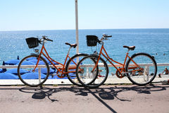 Orange bicycles in Nice France. Two orange bicycles on the Prom des Anglais in Nice France Stock Photo