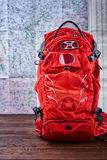 Orange big hiking backpack for the travelling against map background. Stock Photo