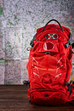 Orange big hiking backpack for the travelling against map background. Royalty Free Stock Images