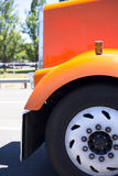 Orange big rig semi truck hood fender and wheel Royalty Free Stock Photo