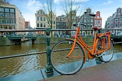 Orange bike along the canals in Amsterdam the Netherlands royalty free stock image